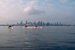 Vancouver, British Columbia, Canada, sea kayakers cross Burrard Inlet, city skyline, 2002, model released,