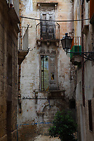 Taranto: In the historical center, the view of a suggestive alley, with the partially broken windows and balconies on the wall of the old building in the background, a cable that crosses it, a street-lamp, and some bed sheets or curtains that were spread out to dry in the air.  One of the window on the (once rose colored) brick wall in the background is partially still reflecting and partially bricked over.