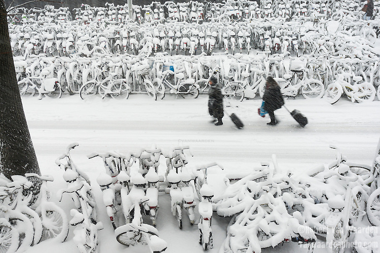 Two women drag luggage past the snow covered bikes in Amsterdam, the Netherlands.