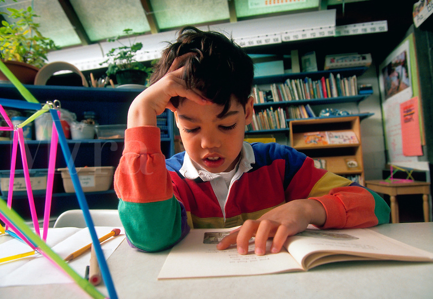 A male elementary student reads in a classroom.