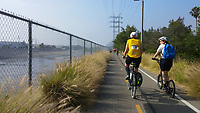 Heading south on the Los Angeles River Greenway Trail from Griffith Park at the start of the 2017 (17th annual) Los Angeles River Ride.  Many bicyclists can be seen ahead of Holland on his kick scooter and Michelle on her Terry Burlington city bike.  The watery riverbed can be seen to the left of the trail, which is lined with large grasses in this area.
