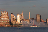 """WEEHAWKEN, NJ - JULY 4: FDNY fire boat Marine 1 """"John D. McKean"""" puts on a water show on the Hudson river, with the Empire State Building and Manhattan skyline in the background, prior to the annual Macy's Fourth of July fireworks on Saturday, July 4, 2009."""