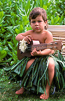 Small toddler holding a ukulele and wearing a ti-leaf skirt with naupaka in background.