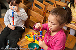 Education preschool 3-4 year olds boy and girl building separate peg towers using opposite hands (right hand or left hand) to add to construction