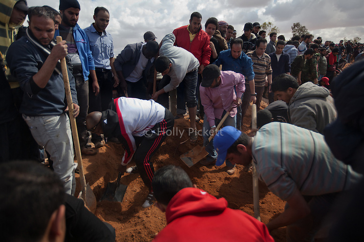 Men cover graves with dirt during a mass funeral for 20 people, killed during fighting between opposition rebels and loyalist forces of Col. Muammar Qaddafi, in Benghazi, Libya, March 20, 2011. The main hospital in Benghazi reported around 50 dead fighters and civilians the previous day and at least 35 on Sunday.