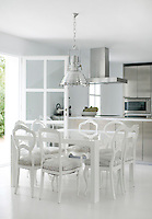 The upholstered dining chairs introduce a subtle pattern into the all white design of the kitchen/dining area