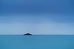 A small island at dawn off the coast at Dunedin in New Zealand