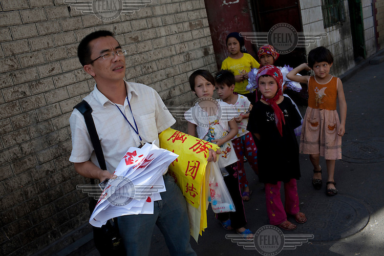 """A Han Chinese official from the local government puts up posters saying """"Stay away from rumours, remain calm, promote ethnic harmony"""". Ethnic violence between the Uighur and Han Chinese erupted in the city a few days earlier.."""