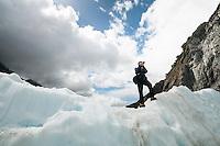 Tourist taking photographs on Franz Josef Glacier, Westland NP, West Coast, New Zealand