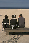 Rio de Janeiro, Brazil. Two maids and a security guard or driver taking a break sitting on a concrete bench on Copacabana Beach.