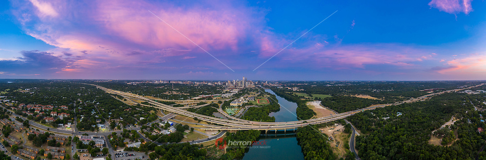 """On a beautiful summer's evening, this aerial panorama photograph of downtown Austin and the skyline taking from the Zilker Clubhouse over Lady Bird Lake shows pink cloud formations sometimes called the """"violet crown"""" found above the Austin Cityscape. Inset, the Mopac Loop 1 expressway is Austin busiest highway in Austin's transportation corridor. In the far distance, the """"Jenga Tower"""" (formally known as the Independent) tops out at 685' and is the tallest highrise in Austin's ever booming skyline, narrowly eclipsing the Austonian (683')."""