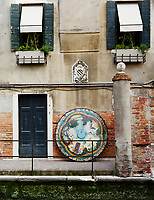 The weathered exterior of Lars Rachen's Venetian apartment, with his Fornasetti table top propped against the wall