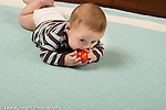 5 month old baby boy on stomach holding toy with both hands, mouthing and biting it