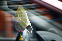A mask hangs off of a rear view mirror of a car parked in front of Children's Hospital in the Bloomfield neighborhood on Tuesday April 14, 2020 in Pittsburgh, Pennsylvania. (Photo by Jared Wickerham/Pittsburgh City Paper)