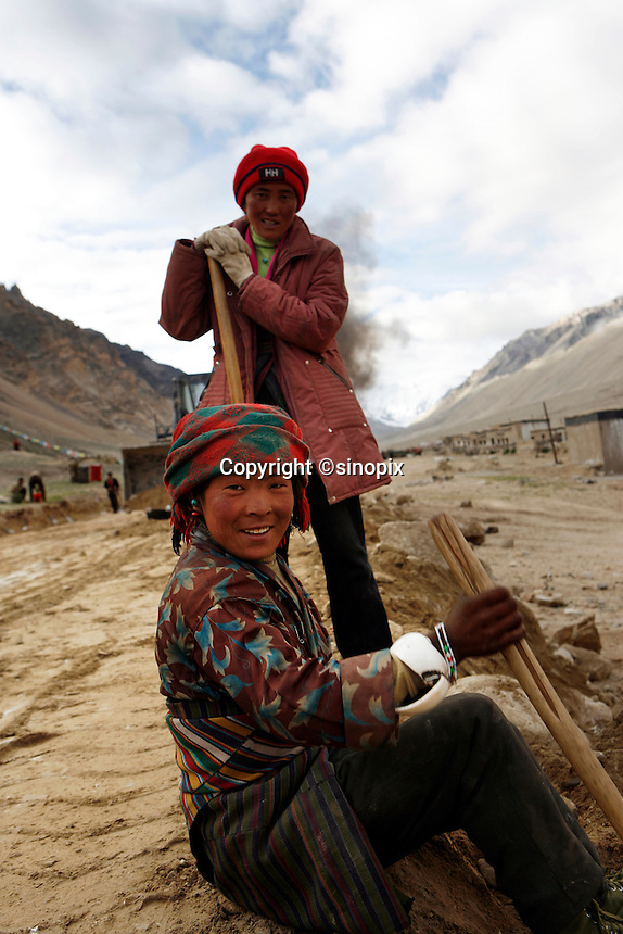 """China started building a controversial 67-mile """"paved highway fenced with undulating guardrails"""" to Mount Qomolangma, known in the west as Mount Everest, to help facilitate next year's Olympic Games torch relay./// Two young women work with a shovels building the road to Everest Base Camp.<br /> Tibet, China<br /> July, 2007"""