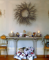 Beneath a console table in the living room presents are piled high waiting to be unwrapped
