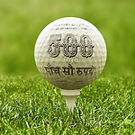Close-up view of golf ball covered with Indian five hundred Rupee note