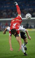Jacek Bak of Poland sails over the head of Miroslav Klose of Germany at FIFA World Cup Stadium, Dortmund, Germany, June 14, 2006.