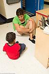 Education Preschool 3 year olds female teacher sitting with sad boy helping him with emotions