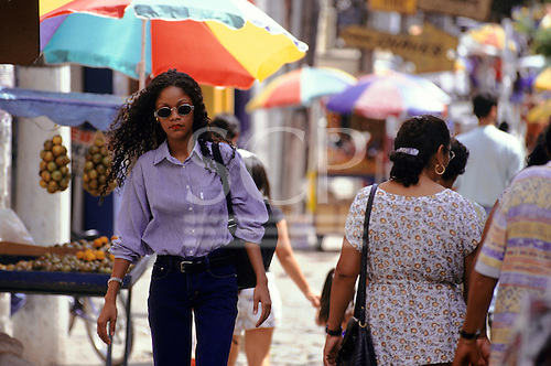 Manaus, Brazil. Street scene; girl with long black curly hair and sunglasses with colourful umberellas behind. Amazonas State.