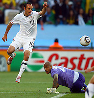 Landon Donovan of USA skips over a challenge from Rais M'Bolhi goalkeeper of Algeria. USA defeated Algeria 1-0 in stoppage time in the 2010 FIFA World Cup at Loftus Versfeld Stadium in Pretoria, Sourth Africa, on June 23th, 2010.