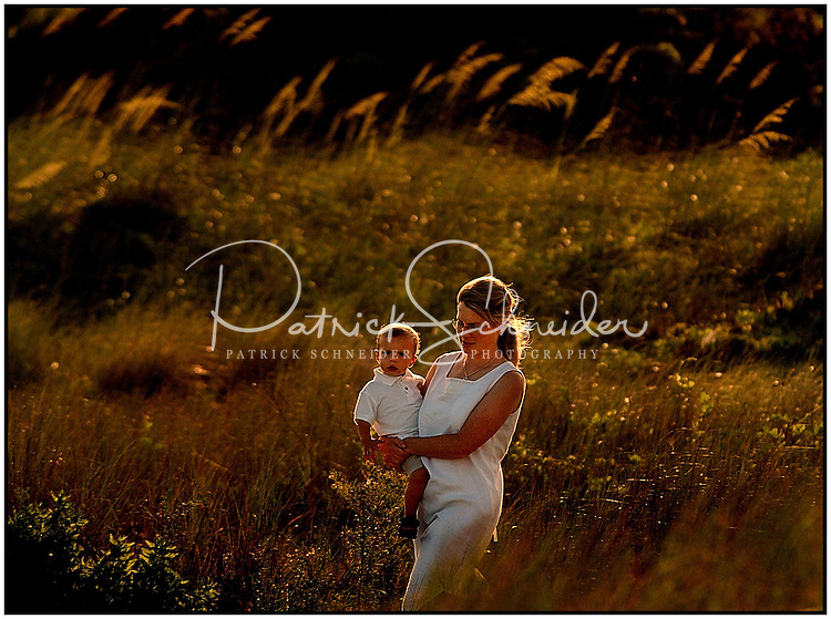 A mother carries her son past a field of beach grass. Nice light from the setting sun. Model released image.