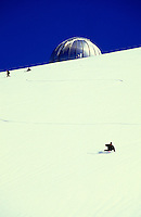 Snowboarding on the slopes of Mauna Kea with the observatory and brilliant blue sky in background.