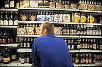 Milano, un ragazzo sceglie le birre dallo scaffale di un supermercato --- Milan, a young man choosing the beers on the shelves of a supermarket