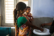11 months old Sita is seen in a playful mood as her mother, Asha Devi washes her face before giving her a dose of RUTF at the government health centre in  Hanuman Nagar, Saptari, Nepal.