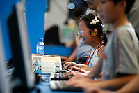 A young girl laughs out while playing a computer game at the 2006 China Joy Digital Entertainment Expo in Shanghai, China. China has one of the fastest growing online gaming market in the world with revenue expected to reach 750 million euros in 2006..