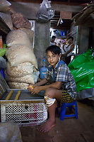 """Ko Min Min*, 14, baking cakes. """"I started working at Nila's* house about 3 months ago. I don´t go to school anymore, but my mother wants me to continue my education. I am not interested to return to school. I now work here, about 10-12 hours a day. We bake cakes which are sold at the local markets. The income is fine for me and I don´t find this work too tiring. I am from a village nearby and support my family with this income"""", tells Ko Min Min*."""