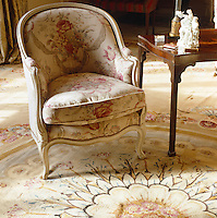 An elegant armchair upholstered in a pale floral fabric
