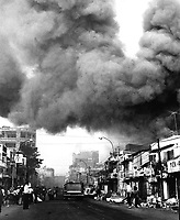 Black smoke covers areas of the capital city and fire trucks rush to the scenes of fires set during attacks by the Viet Cong during the festive Tet holiday period.  Saigon, 1968.  (USIA)<br /> EXACT DATE SHOT UNKNOWN<br /> NARA FILE #:  306-MVP-25-2<br /> WAR & CONFLICT BOOK #:  418