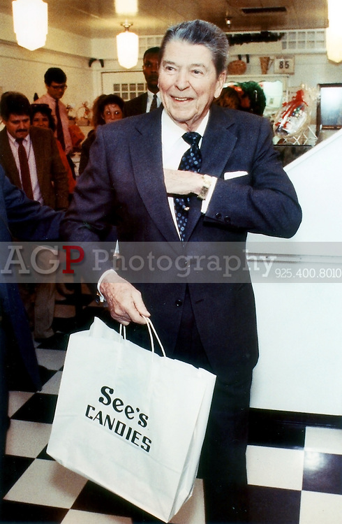Former U.S. President Ronald Reagan reaches into hit coat pocket as he walks out of a Sees Candy store in Century City, Calif December 8, 1989. Reagan was Christmas Shopping for his wife Nancy. (photo by Alan Greth)
