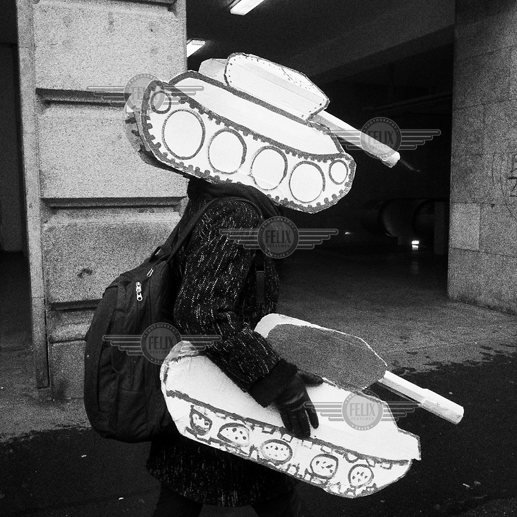 A young girl with a paper tank head piece heading to a rally commemorating the 1989 Velvet Revolution.