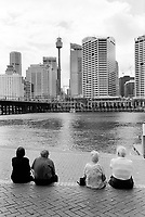 Australia. New South Wales. Sydney. Darling Harbour is a harbour adjacent to the city centre. It is made up of a large recreational and pedestrian precinct that is situated on western outskirts of the Sydney Central Business District (CBD). People sit on stairs and look at the skyline. 16.3.99  © 1999 Didier Ruef