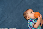 7 month old baby boy holding toy ball and biting it looking to side
