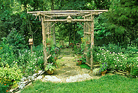 Handmade Cedar archway, arbor, leading into shade garden on large stone pathways to benches