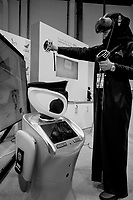 United Arab Emirates (UAE). Abu Dhabi. Unmanned Systems Exhibition (UMEX 2020). The humanoid robot is helping inspection clearance and clarification on booth of Abu Dhabi Department of Finance, General Administration of Customs. A humanoid robot is a robot with its body shape built to resemble the human body. The design may be for functional purposes, such as interacting with human tools and environments. An Emirati woman with a black abaya tests the virtual reality headset used for training various platforms for customs operations powered by artificial intelligence (AI) to access and evaluate process. A virtual reality headset is a head-mounted device that provides virtual reality for the wearer. Virtual reality (VR) headsets are widely used with  simulators and trainers. In computer science, artificial intelligence (AI), sometimes called machine intelligence, is intelligence demonstrated by machines. The United Arab Emirates (UAE) is a country in Western Asia at the northeast end of the Arabian Peninsula. 23.02.2020  © 2020 Didier Ruef