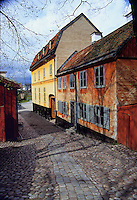 A fine art travel image of old Swedish buildings, with a cobblestone street leading into the frame between orange and yellow historic buildings on the right and a reddish wooden historic structure on the left