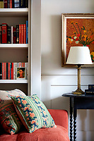 Walls and woodwork in the living room have been painted a stone grey, presenting a muted backdrop for bookshelves and artwork