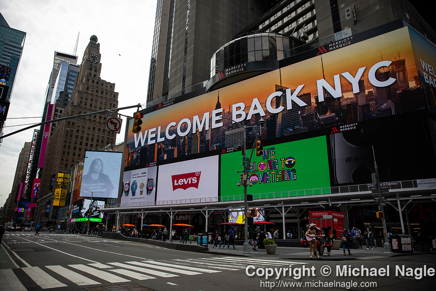 Pedestrians pass through Times Square displaying a Welcome Bank NYC message on monitors in New York on Wednesday, April 14, 2021. Photographer: Michael Nagle