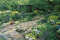 Beautiful stone path laid by hand to wooden arch in blooming garden