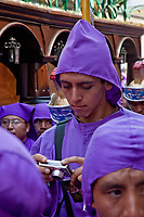 Antigua, Guatemala.  A Cucurucho Prepares his Camera for a Photo while Escorting a Float (Anda) in a Religious Procession during Holy Week, La Semana Santa.