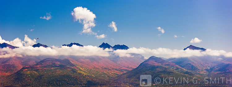 Small plane flying in front of the Chugach Mountains, Fall, Anchorage, Southcentral Alaska, USA.