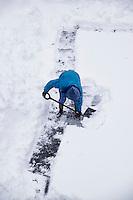 Adult shoveling snow after winter storm.