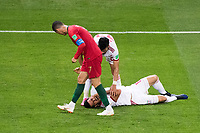 SARANSK, RUSSIA - June 25, 2018: Iran defender Morteza Pouraliganji lays on the ground while attended to by teammate Ramin Rezaeian after being hit by Portugal's Cristiano Ronaldo in their 2018 FIFA World Cup group stage match at Mordovia Arena.