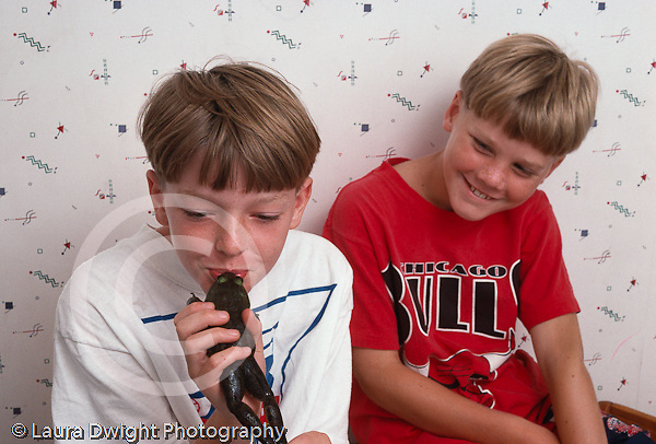 9 year old boys friends  laughing and playing with frog they found outside horizontal Caucasian