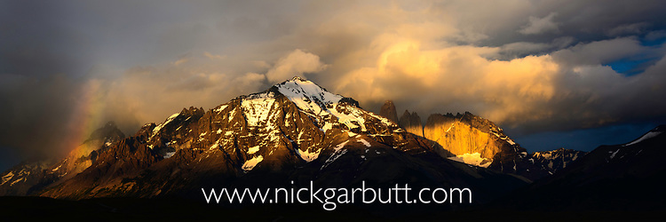 Dramatic light with a rainbow at sunrise on the Towers and Central Massif of Torres del Paine. Torres del Paine National Park, Patagonia, Chile.