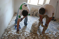Operai edili mentre ristrutturano un appartamento di un vecchio palazzo..Construction workers restructure an apartment in the old building..